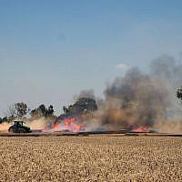 Illustration : Un agriculteur israélien éteint un incendie dans son champ qui a été allumé par un cerf-volant incendiaire envoyé de Gaza aux abords du kibboutz de Nahal Oz, dans le sud d'Israël, le 14 mai 2018 (Crédit :  Judah Ari Gross/Times of Israel)