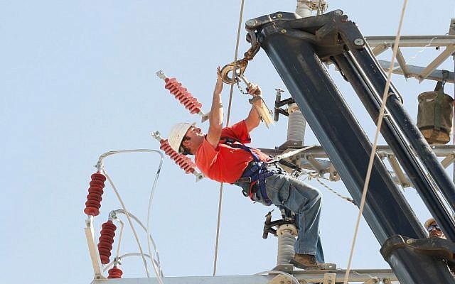 Un employé d'Israel Electric Corporation travaillant sur une ligne électrique. (Roni Schutzer / Flash90)