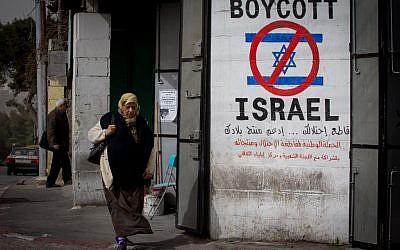 Une Palestinienne marche devant une pancarte appelant au boycott d'Israël dans la ville de Bethléem en Cisjordanie, le 11 février 2015 (Miriam Alster / Flash 90)