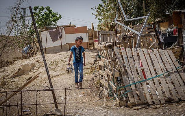Un garçon traverse le village bédouin de Khan al-Ahmar, près de l'autoroute Jérusalem-Mer Morte, le 13 avril 2018. (Yaniv Nadav / Flash90)