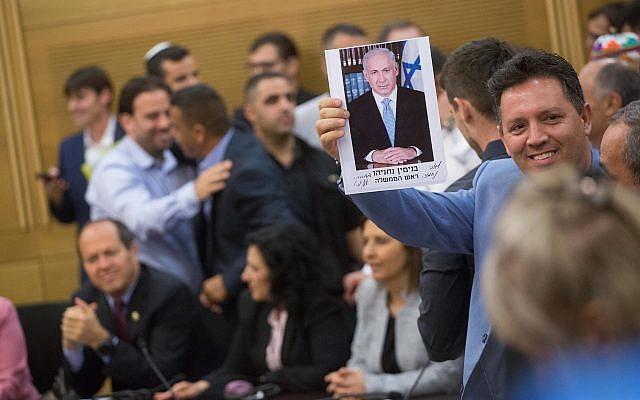 Les partisans du Premier ministre Benjamin Netanyahu tenant sa photo signée, lors d'une réunion du faction du Likoud à la Knesset le 7 mai 2018. (Miriam Alster / Flash90)