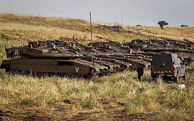 Soldats israéliens observés à côté de chars près de la frontière israélo-syrienne sur le plateau du Golan le 10 mai 2018. (Basel Awidat/Flash90)