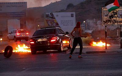Des manifestants palestiniens affrontent les forces de sécurité israéliennes lors d'affrontements survenus aux abords du check-point de Hawara, au sud de la ville de Naplouse, en Cisjordanie, le 14 mai 2018 (Crédit : Nasser Ishtayeh/Flash90)