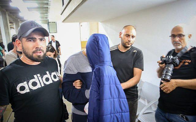 Un homme soupçonné d'avoir tué ses deux soeurs dans leur maison de Jaffa se couvre le visage à son arrivée à la cour des magistrats de Tel Aviv pour une audience de mise en détention, le 17 mai 2018 (Crédit :  FLASH90)