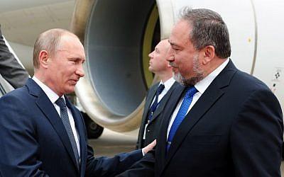 Le ministre des Affaires étrangères Avigdor Liberman salue le président russe Vladimir à l'aéroport Ben-Gurion, lundi  (Crédit : Kobi Gideon/GPO)