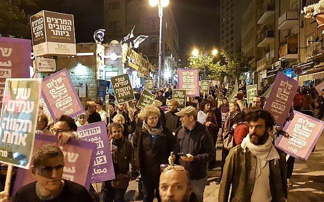 Des manifestants dénoncent le transfert de l'ambassade américaine à Jérusalem durant un défilé dans le centre de Jérusalem le 12 mai 2018 (Autorisation : Standing Together)