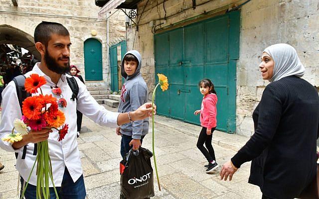 Un activiste de Tag Meir, organisation financée par le New Israel Fund, distribue une fleur à une femme musulmane dans la Vieille Ville de Jérusalem le 13 mai 2018, le jour de Yom Yeroushalayim. (Crédit : Rafi Kutz / Tag Meir)