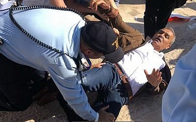 Le député de la Liste arabe unie Jamal Zahalka est plaqué au sol par des policiers israéliens devant la nouvelle ambassade des États-Unis à Jérusalem alors que se déroule la cérémonie d'inauguration du bâtiment le 14 mai 2018. (Avec l'aimable autorisation de la Liste arabe unie)