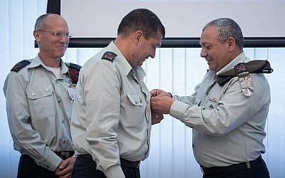 Le chef d'Etat-major Gadi Eizenkot place  son insigne sur la chemise de nouveau chef des opérations de l'armée israélienne, le général de division Aharon Haliva, alors que le chef sortant, le général de division Nitzan Alon les regarde, durant une cérémonie organisée au siège de l'armée, à Tel Aviv, le 21 mai 2018 (Crédit : Armée israélienne)