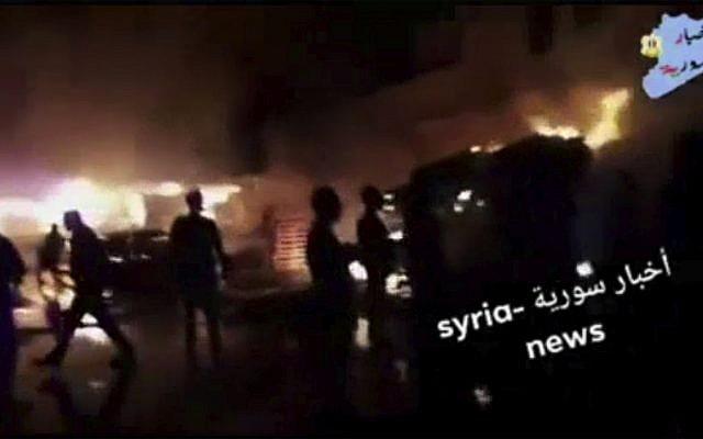 Cette capture d'écran tirée d'une vidéo fournie le 9 mai 2018 par l'agence Syria News montre des personnes debout devant les flammes réveillées après une attaque contre une zone connue pour héberger de nombreuses bases militaires de l'armée syrienne, à Kisweh, au sud de Damas, en Syrie. Mardi. l'Observatoire syrien des droits de l'homme basé en Grande-Bretagne a déclaré que les tirs ciblaient les dépôts et les armes qui appartenaient probablement aux forces iraniennes à Kisweh (Syria News)