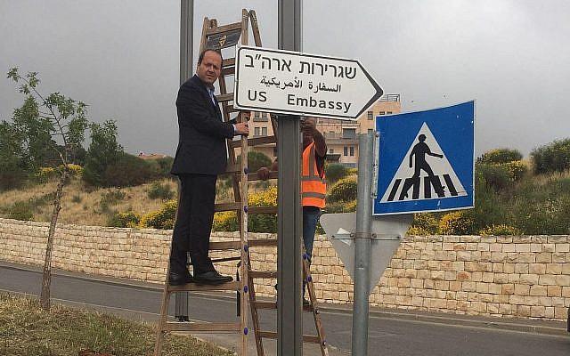 Le maire de Jérusalem Nir Barkat accroche le premier panneau signalant l'ambassade américaine à Jérusalem, le 7 mai 2018 (Crédit : Municipalité de Jérusalem)