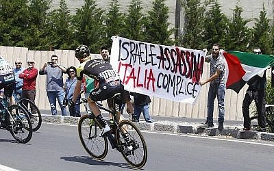 """Des manifestants anti-israéliens brandissent un panneau disant """"Israël assassine, l'Italie complice"""" avant le début de la 4ème étape du Giro d'Italie entre Catania et Caltagirone en Sicile, le 8 mai 2017 (Crédit :  AFP PHOTO / Luk Benies)"""