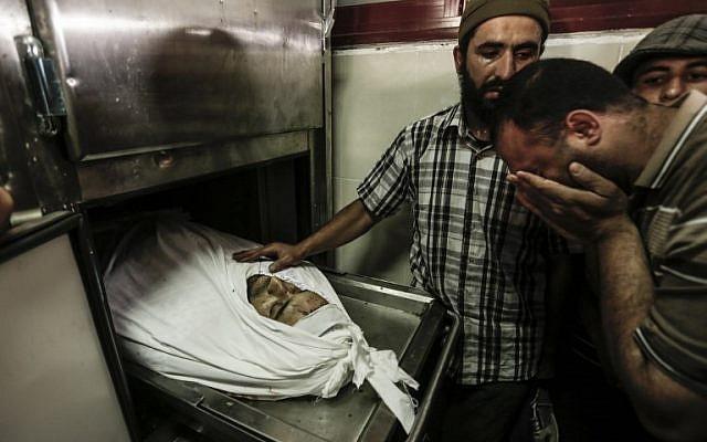 """Un Palestinien pleure près du corps de Mohammed al-Radeia, 30 ans, avant ses funérailles à Beit Lahia, dans le nord de la bande de Gaza, le 28 mai 2018. L'homme palestinien a été tué par les tirs de chars israéliens dans le nord de Gaza plus tôt dans la journée, a déclaré le ministère de la Santé dans l'enclave dirigée par le Hamas. Une porte-parole de l'armée israélienne a déclaré à l'AFP que deux hommes palestiniens ont tenté de franchir la clôture de la frontière """"avec l'intention de mener une attaque"""". (AFP PHOTO / MAHMUD HAMS)"""