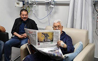 Mahmoud Abbas, président de l'Autorité palestinienne, en convalescence à l'hôpital, lisant un journal au verso duquel figure une caricature représentant un soldat israélien empoisonnant un bébé palestinien, 22 mai 2018. (Agence de presse Wafa)