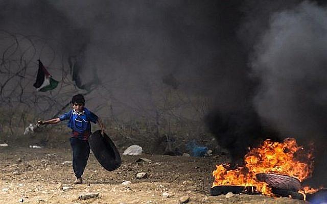 Un enfant palestinien court avec un pneu lors d'affrontements avec les forces israéliennes le long de la frontière avec la bande de Gaza à l'est de la ville de Gaza, le 4 mai 2018 (AFP PHOTO / MAHMUD HAMS)
