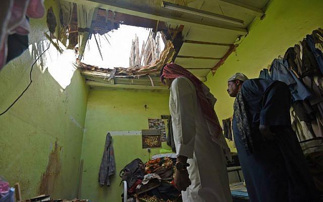 Photo prise le 28 mars 2018 à Um Al-Hammam, un quartier de Riyadh : des ouvriers égyptiens inspectent les dégâts causés par des débris de missiles lancés par les rebelles yéménites, interceptés au dessus de la capitale saoudienne. (Crédit : AFP FAYEZ NURELDINE)