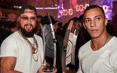 Les rappeurs allemands Kollegah, à gauche, et Farid Bang posent avec leur  trophée de l'Echo obtenu dans la catégorie hip/hop musique urbaine, le 12 avril 2018 (Crédit : AFP PHOTO / dpa / Jens Kalaene0