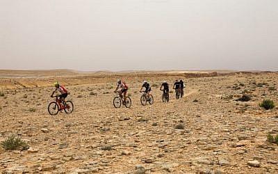 Des cyclistes traversent le désert du Néguev à Machtesh Ramon, le 6 mai 2018. (Crédit :AFP / MENAHEM KAHANA)