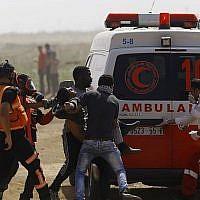 Un Palestinien blessé est évacué durant les affrontements avec les forces israéliennes sur la frontière avec Gaza, aux abords de Jabaliya, le 11 mai 2018 (Crédit :  AFP PHOTO / MOHAMMED ABED)