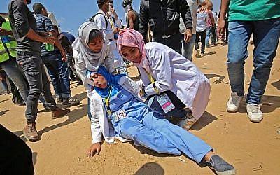 Razan al-Najjar (D), une secouriste palestinienne de 21 ans, soigne une collègue blessée lors d'affrontements près de la frontière avec Israël, à l'est de Khan Younès, dans le sud de la bande de Gaza, le 15 mai 2018. (AFP/ DIT KHATIB)