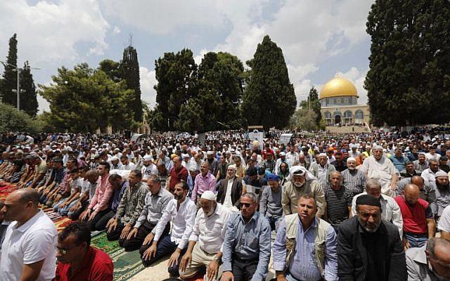 Les fidèles musulmans prient près du Dômle du rocher et de la mosquée Al-Aqsa, situés dans le complexe du mont du Temple à Jérusalem, pendant les troisièmes prières du vendredi du mois sacré du Ramadan, le 1er juin 2018 (Crédit :  AFP Photo/Ahmad Gharabli)