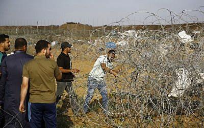 Un manifestant palestinien coupe une section de fil barbelé sur la clôture frontalière entre Israël et la bande de Gaza, à l'est de Jabalia, le 1er juin 2018 (Crédit :/ AFP PHOTO / Mohammed ABED)