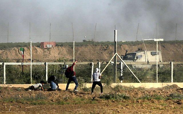 Un Palestinien jette des pierres sur les forces israéliennes alors que de la fumée s'élève des pneus brûlés durant une manifestation le long de la frontière avec la bande de Gaza, à l'est de Gaza city, le 1er juin 2018 (Crédit :  / AFP PHOTO / Mahmud Hams)
