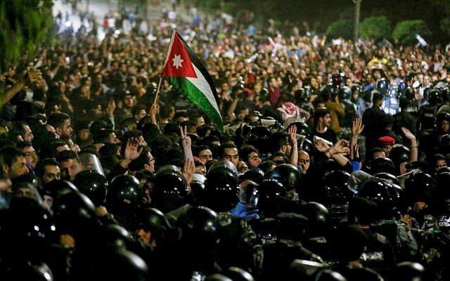 Des membres de la gendarmerie et des forces de sécurité jordaniennes sont en état d'alerte alors que des manifestants scandent des slogans et brandissent un drapeau national lors d'une manifestation devant le bureau du Premier ministre dans la capitale Amman le 2 juin 2018. (AFP PHOTO / Khalil MAZRAAWI)