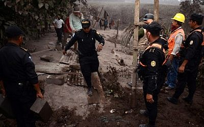 La police dans le village d'El Rodeo, à 35 km au sud de Guatemala City, après l'éruption du volcan de Fuego, le 3 juin 2018. (Crédit : AFP / NOE PEREZ)