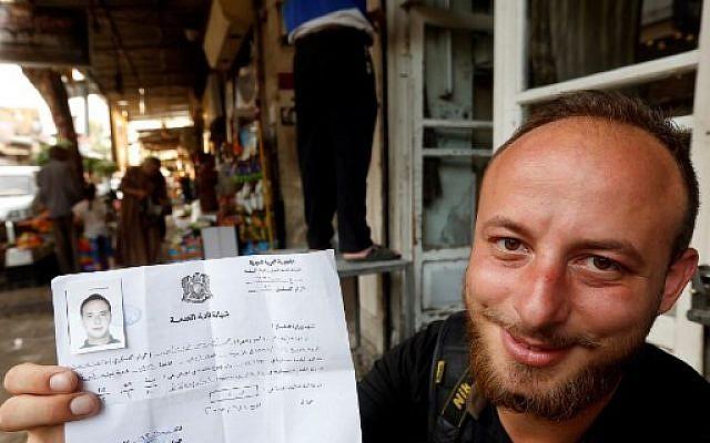 Le combattant syrien Mohammad Damour brandit le document attestant de sa démobilisation de l'armée syrienne, à Damas,le 4 juin 2018. (Crédit : AFP / LOUAI BESHARA)