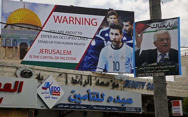 Cette photo du 5 juin 2018 montre une affiche érigée dans la ville de Hébron, en Cisjordanie, appelant au boycott de la star du football Lionel Messi (g) à côté d'un portrait du président de l'Autorité palestinienne Mahmoud Abbas. (AFP PHOTO / HAZEM BADER)