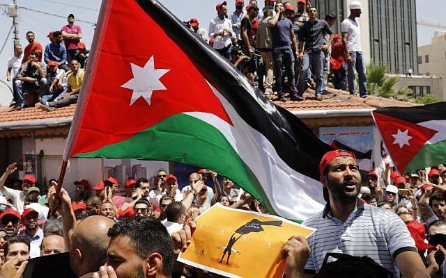 Les manifestants jordaniens brandissent des drapeaux et scandent des slogans durant un rassemblement anti-austérité à Amman, le 6 juin 2018 (Crédit : / AFP PHOTO / AHMAD GHARABLI)