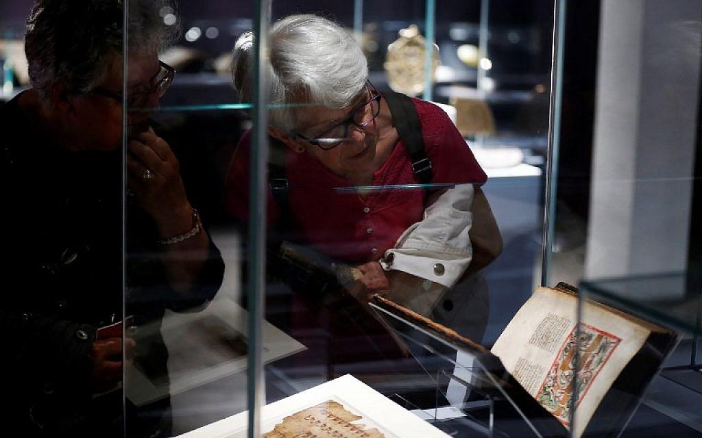 """Les visiteurs regardent un livre historique présenté dans l'exposition """"Savants et croyants, les Juifs d'Europe du Nord au Moyen-Age"""" au musée des Antiquités de Rouen, en France, le 7 juin 2018. (Crédit : AFP / CHARLY TRIBALLEAU)"""