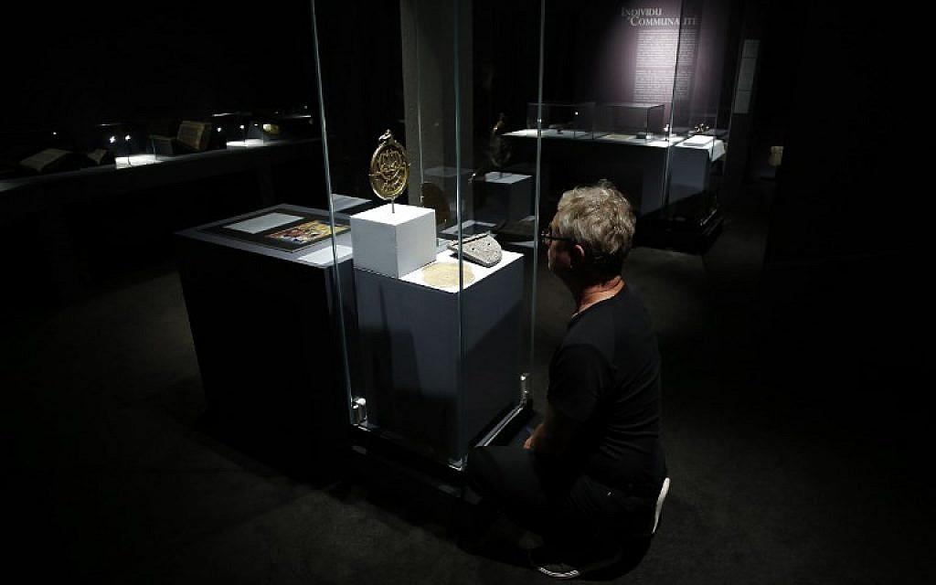 """Un visiteur regarde les artefacts historiques présentés dans l'exposition """"Savants et croyants, les Juifs d'Europe du Nord au Moyen-Age"""" au musée des Antiquités de Rouen, en France, le 7 juin 2018. (Crédit : AFP / CHARLY TRIBALLEAU)"""