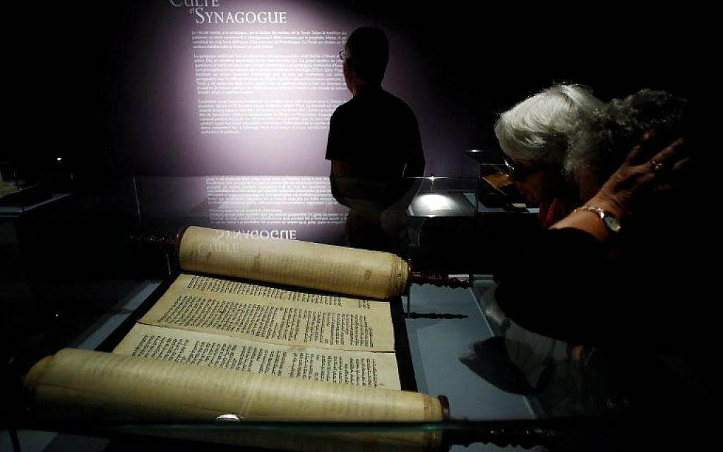 """Les visiteurs regardent un rouleau de Torah présenté dans l'exposition """"Savants et croyants, les Juifs d'Europe du Nord au Moyen-Age"""" au musée des Antiquités de Rouen, en France, le 7 juin 2018. (Crédit : AFP / CHARLY TRIBALLEAU)"""