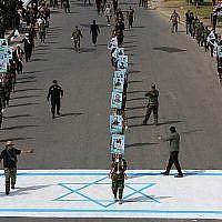 """Des paramilitaires chiites alliés à l'Iran marchent sur un drapeau israélien dessiné sur la chaussée lors d'un rassemblement pour marquer la """" Journée Al-Quds """" (Jour de Jérusalem) initialement lancé par l'Iran en 1979 et tombant le dernier vendredi du mois sacré du Ramadan, à Bagdad, la capitale irakienne, le 8 juin 2018. (AFP Photo/Ahmad al-Rubaye)"""