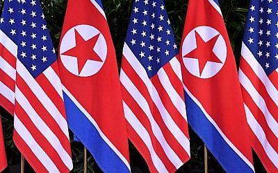 Les drapeaux nord-coréen et américain côte à côte sur le site où se rencontrent le président américain Donald Trump et le leader nord-coréen  Kim Jong Un pour leur sommet historique Etats-Unis-Corée du Nord, au Capella Hotel, sur l'île de Sentosa de Singapour, le 12 juin 2018  (Crédit : AFP PHOTO / SAUL LOEB)