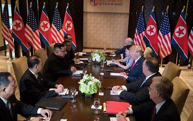 Le président américain Donald Trump, 3ème à droite, et le leader de la Corée du nord, Kim Jong Un, 3ème à gauche, avec leurs délégations respectives lors du sommet Etats-Unis-Corée du nord à l'hôtel Capella de l'île de Sentosa à Singapour, le 12 juin 2018  (AFP PHOTO / SAUL LOEB)