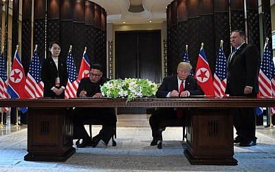 Le président américain Donald Trump (2e à droite) et le dirigeant nord-coréen Kim Jong Un (2e à gauche) signent des documents alors que le secrétaire d'État américain Mike Pompeo (à droite) et la sœur du dirigeant nord-coréen Kim Yo Jong (à gauche) assistent à une cérémonie de signature lors du sommet États-Unis-Corée du Nord à l'hôtel Capella sur l'île de Sentosa, à Singapour, le 12 juin 2018. (Saul Loeb/AFP)