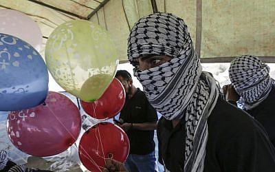 Des Palestiniens masqués préparent des ballons équipés de produits inflammables à envoyer en Israël depuis la bande de Gaza à al-Bureij, au centre de l'enclave, le 14 juin 2018 (Crédit :  / AFP PHOTO / MAHMUD HAMS