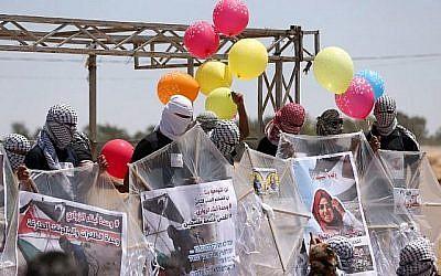 Des manifestants palestiniens préparent des cerfs-volants chargés de matériel inflammable pour les faire voler vers Israël, à la frontière entre Israël et Gaza, à al-Bureij, au centre de la bande de Gaza, le 14 juin 2018. (AFP PHOTO / MAHMUD HAMS)