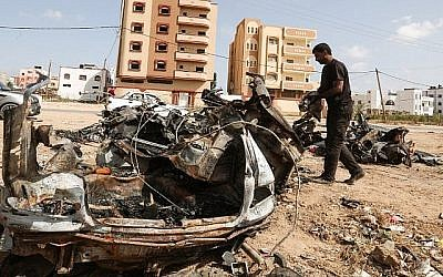 Un Palestinien inspecte une voiture détruite après une frappe israélienne à Gaza City qui, selon l'armée, a été prise pour cible parce qu'elle appartenait à un responsable des attaques aux cerfs-volants et aux ballons incendiaires sur le sud d'Israël, le 17 juin 2018 (Crédit : Mahmud Hams/AFP)