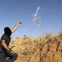 Un Palestinien masqué lance un ballon chargé de matières inflammables en direction d'Israël depuis la ville de Rafah, au sud de Gaza, le 17 juin 2018. (AFP Photo/Said Khatib)