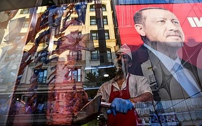 Tandis qu'un boucher tranche de la viande, l'on aperçoit le reflet d'un portrait du président turc Recep Tayyip Erdogan dans la fenêtre d'un restaurant turc sur la place Taksim d'Istanbul le 20 juin 2018. (Crédit : AFP / Bulent Kilic)