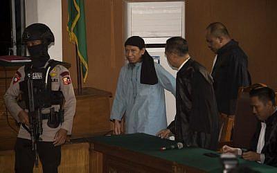 Un agent de police indonésien escorte Aman Abdurrahman, cerveau de l'attentat suicide de Jakarta en 2016, au tribunal de Jakarta, le 22 juin 2018. (Crédit : AFP / BAY ISMOYO)