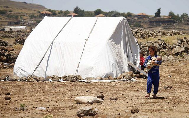 Une jeune fille syrienne déplacée de la province de Daraa, fuyant les bombardements des forces pro-gouvernementales, transporte un nourrisson dans un camp de fortune dans la province de Quneitra, au sud-ouest de la Syrie, près de la frontière avec le plateau du Golan, le 22 juin 2018. (AFP PHOTO / Mohamad ABAZEED)