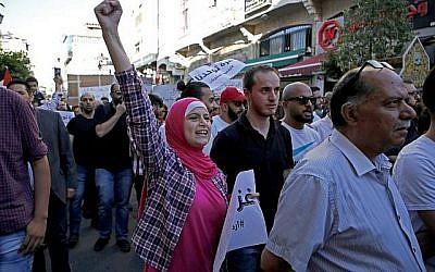 Les Palestiniens participent à une manifestation appelant à la levée des sanctions contre la bande de Gaza, dans la ville de Ramallah en Cisjordanie, le 23 juin 2018. (Crédit : AFP / ABBAS MOMANI)
