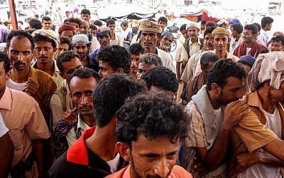 Des civils yéménites font la queue pour recevoir de la nourriture, après avoir fui le conflit à Hodeida, le 26 juin 2018. (Crédit : ESSA AHMED / AFP)
