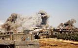 De la fumée émane des bâtiments durant une frappe des forces du régime syrien sur la ville de Busra al-Harir, à l'est de a province de Deraa, le 24 juin 2018. (Crédit : AFP/ Mohamad ABAZEED)