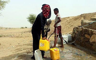 Des Yéménites qui ont fui le conflit à Hodeida, prennent de l'eau dans un village au nord de la province de Hajjah, le 26 juin 2018. (Crédit : ESSA AHMED / AFP)